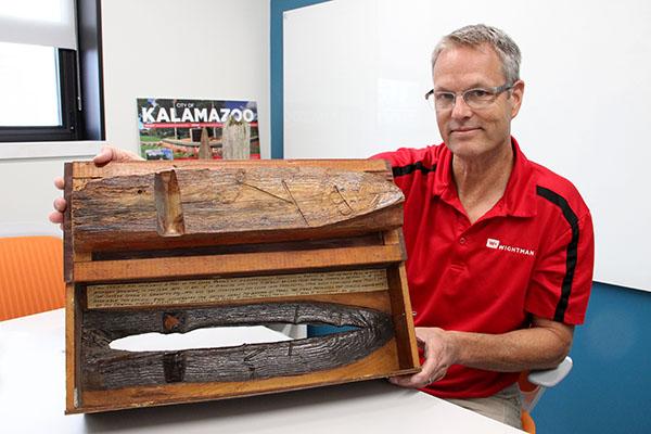 Gary Hahn, Regional Survey Manger in Wightman's Kalamazoo office,  holds up an artifact of Michigan's land survey history