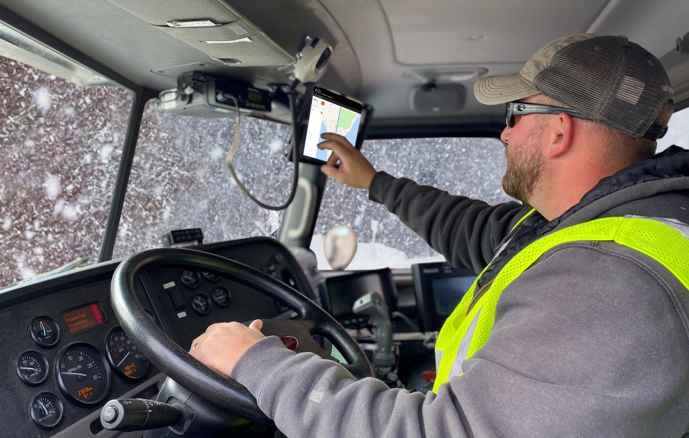 Snowplow Truck Interior with Driver Using GIS in Snowstorm
